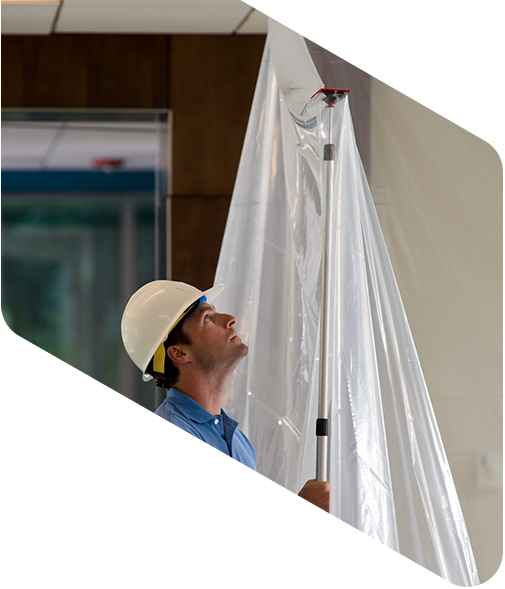 Keeping it clean with ZipWall Dust Barriers | Surface Protection | Construction worker putting up a ZipWall pole with polythene attache | Blog | Univar SC